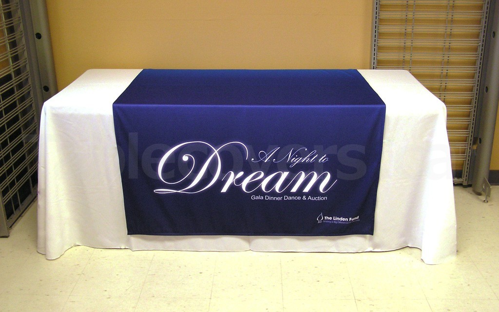 48 inch by 80 inch custom dye sublimation printed table runner on a 6 foot display table